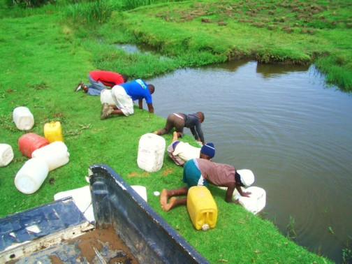 filling the 25L jerry cans from the river