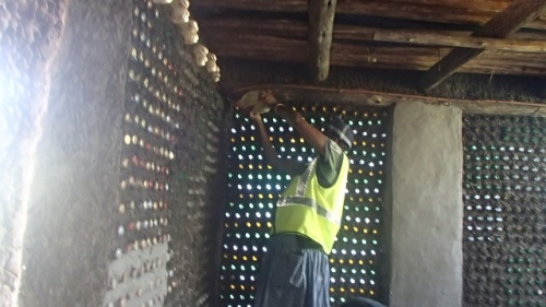 Nophumzile Macubeni works on a decorative wall made from recycled materials